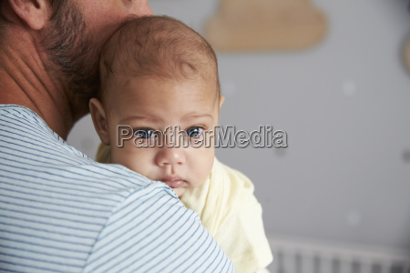 close up of father comforting newborn