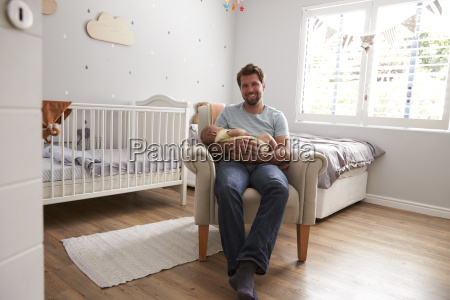 father sitting in nursery chair holds