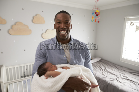 portrait of father holding newborn baby