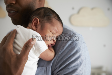 close up of father holding newborn