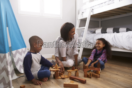 mother and children playing with building