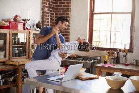happy hispanic couple dancing in kitchen