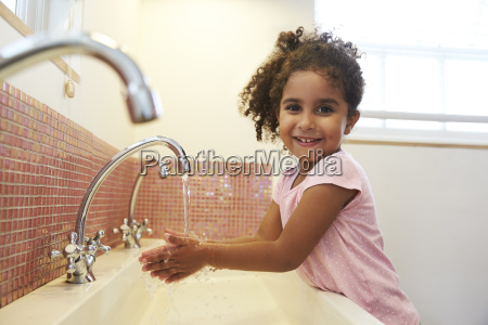 female pupil at montessori school washing