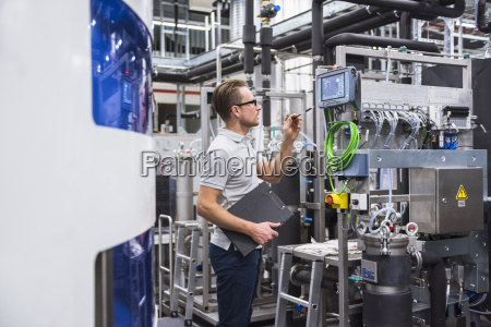 man looking at screen in factory