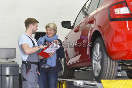 car mechanic with client in workshop