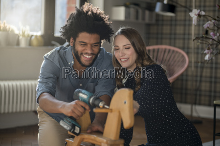 smiling couple mounting rocking horse with