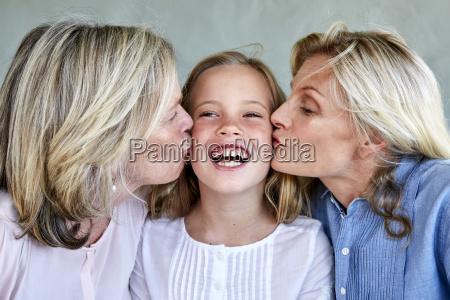 portrait of happy little girl kissed