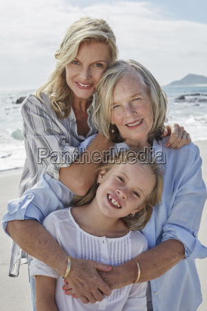 mother daughter and grandmother embracing on