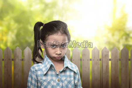 sad asian kid in blue clothes
