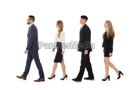 multiracial businesspeople walking in row