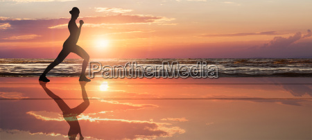 womans silhouette doing exercise at beach
