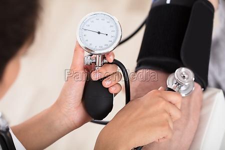 doctor measures her blood pressure
