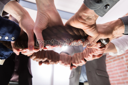 hands holding rope forming a circle