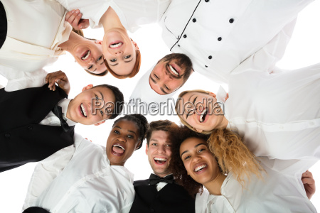 smiling restaurant staff standing against white
