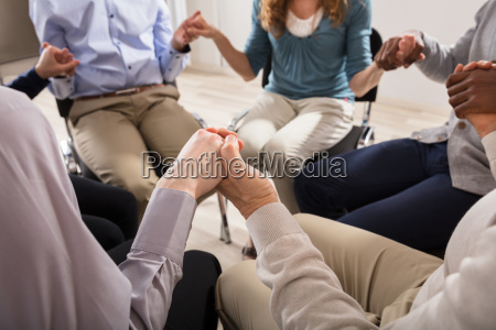 people holding each others hand praying