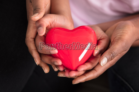 mother and daughter holding red heart