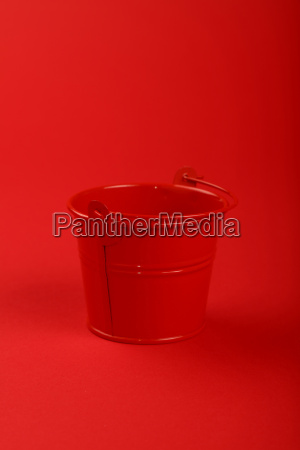 one small metal bucket on red