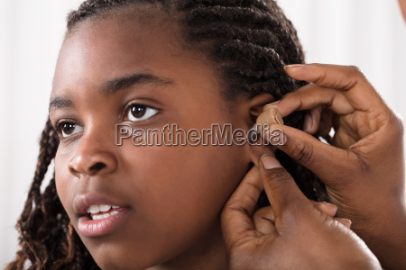 doctor putting hearing aid in patients