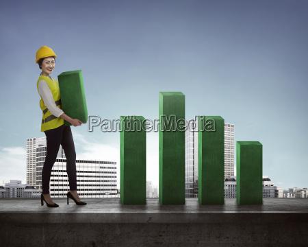 asian business woman lifting block of