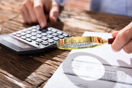 accountant using magnifying glass while calculating