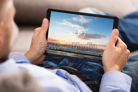 man watching video on digital tablet