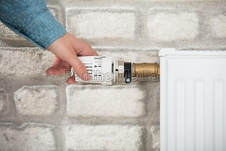 person adjusting temperature of radiator