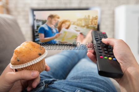 woman holding cupcake and remote control