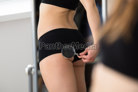 reflection of woman checking her buttock