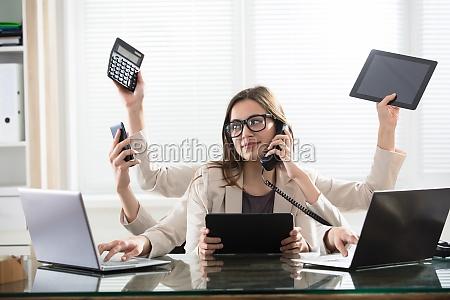 multitasking businesswoman in office