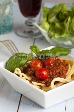 portion of spaghetti bolognese with salad