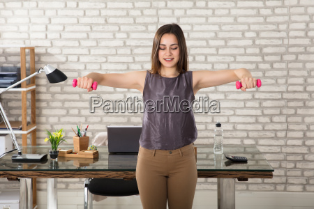 businesswoman, doing, exercise, in, office - 22643609
