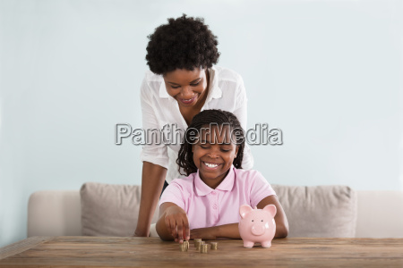 girl, with, mother, inserting, coins, in - 22643483