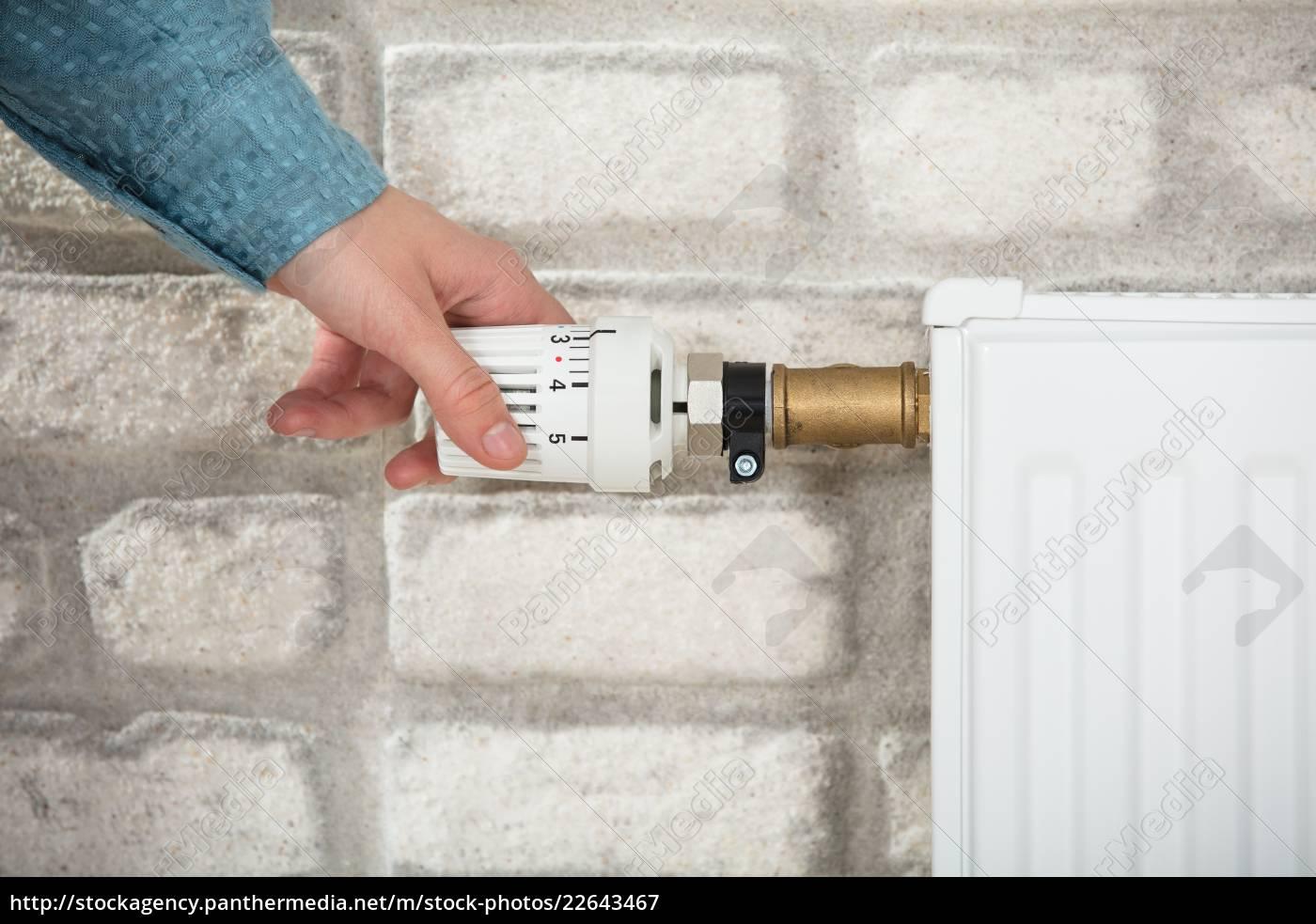 person, adjusting, temperature, of, radiator - 22643467