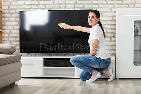 woman, wiping, the, television, screen, at - 22643521