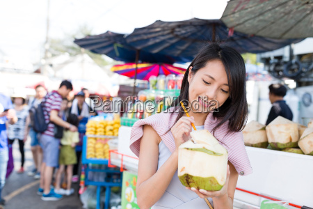 woman enjoy coconut juicy in street