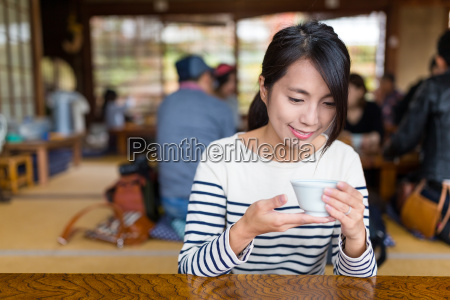 woman, drinking, tea, in, a, restaurant - 22648147