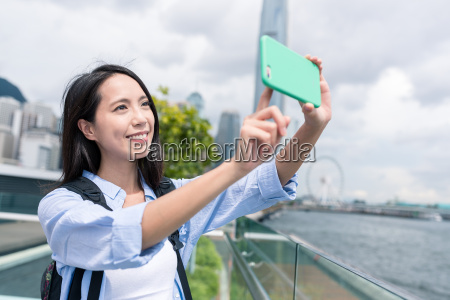 woman, taking, photo, on, cellphone, in - 22648307