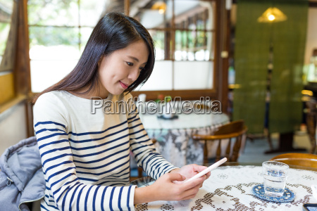 woman, using, mobile, phone, in, cafe - 22648199