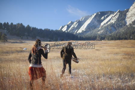 musicians walking on field with mountains