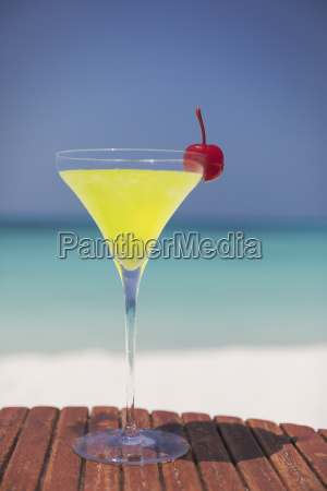 yellow cocktail with cherry in martini