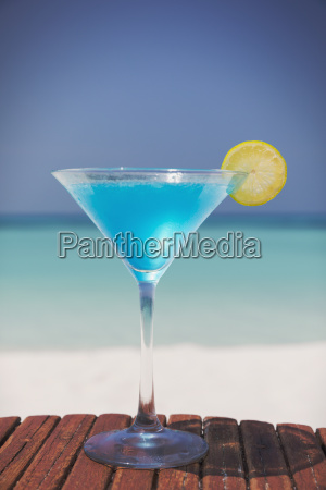 blue cocktail with lemon slice in