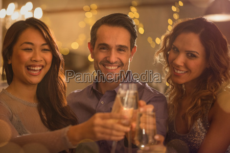 portrait smiling friends toasting wine glasses
