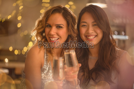 portrait smiling women friends toasting champagne