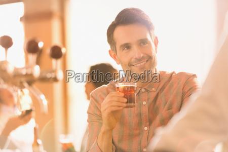 smiling man drinking cocktail at bar