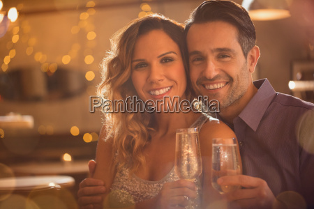portrait smiling couple drinking champagne