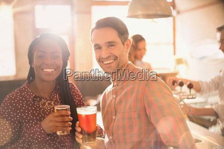 portrait smiling couple drinking beer in