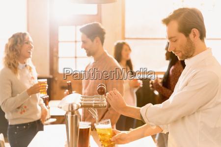 bartender pouring beer at beer tap