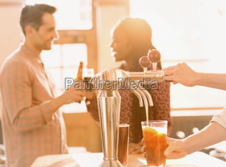 couple drinking beer behind bartender pouring