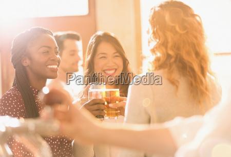 smiling women friends toasting beer glasses