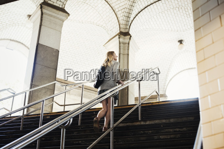a woman walking up the steps
